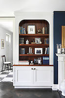 Detail of the painted, bespoke cabinetry in the reception room, with its curved joinery and interior left as polished wood to give a richer patina to the room