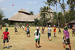 Boys and girls students playing football during break with 'Heart of School in background'<br />