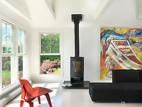 A contemporary black wood burning stove is a central feature in the all-white living area