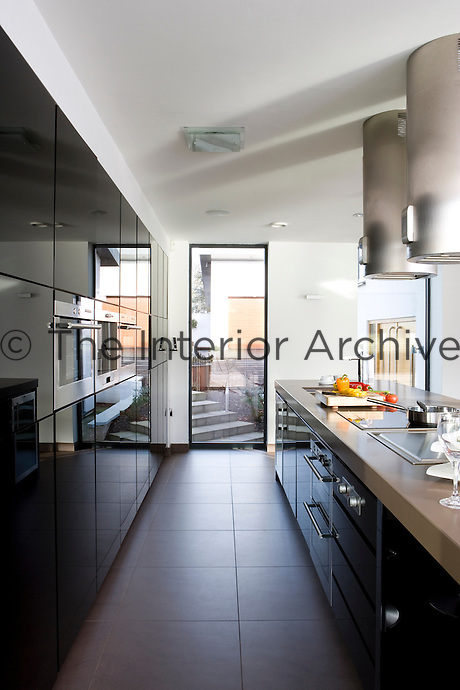 In the kitchen/living area grey stone floors contrast with cupboards faced in black high-gloss parapan