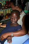 A young Costa Rican girl sits on her mother's lap in a Limon market. ..Costa Rica, Caribbean, Port, Limon, shop, markets, goods