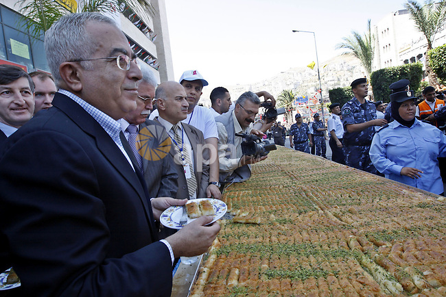 Palestinian prime minister Salam Fayad opens the ceremony of the biggest dish of traditional sweets Konafa into the Guinness Book of Records in the West Bank city of Nablus on July 18 2009. Photo by  Photo by Mustafa Abu Dayeh \ pool
