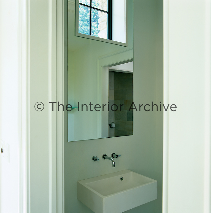 View into a small white bathroom with a contemporary basin and a large mirror