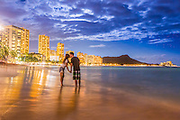 A couple on their honeymoon kiss under a full moon at Waikiki Beach, O'ahu.