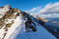Hiker on moutain pass at Ågskaret overlooking Å, Moskenesøy, Lofoten Islands, Norway