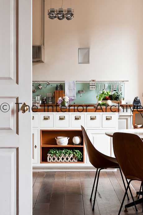 This kitchen features a glass splashback with kitchen utensils hanging from a slim metal rail and a wooden island unit with storage