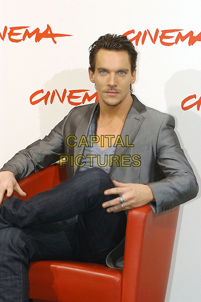 """JONATHAN RHYS MEYERS.Photocall for film  """"Agust Rush"""" during the .Rome International Film Festival, Rome, Italy, .October 20th 2007..half length sitting red chair grey suit jacket top v-neck chest  beard.CAP/CAV.©Luca Cavallari/Capital Pictures."""