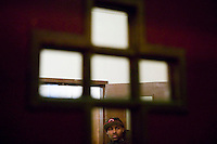 New York, USA - A congregation member waits in the lobby of the Greater Hood Memorial AME Zion Church, home of the Hip-Hop Church, in Harlem, New York, USA, after mass, 24 February 2005. Photo Credit: David Brabyn.