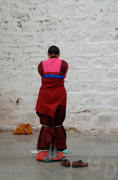 A women facing the wall for prayers at the The Jokhang Temple it is one of Tibet's holiest shrines, originally built in 647 A.D. in celebration of the marriage of the Tang Princess Wencheng and the Tubo King Songtsen Gampo. In front of the gate is a stone Tablet of Unity from the Tang Dynasty; inscribed are both Chinese characters and Tibetan script. Nearby is the stump of the willow tree said to have been planted by Princess Wencheng herself; two younger willow trees now flank the stump of the first tree..