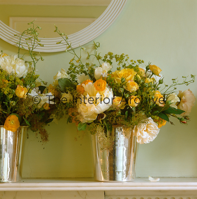 Two small silver vases containing several varieties of yellow rose are arranged on the mantelpiece of a London living room