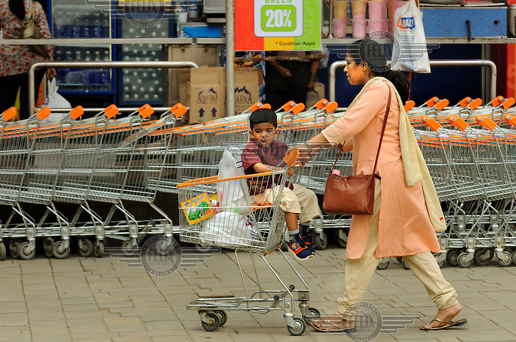 Mother and son shopping with a trolley at High Street Phoenix, a shopping mall in a former textile mill.