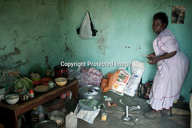 NKANDLA, SOUTH AFRICA - OCTOBER 10: A woman cleans inside her one-roomed mud house next to the new home for South Africa president Jacob Zuma's in his birth village on October 10, 2012 in KwaNxamalala, Nkandla. South Africa.  The South African government is spending R240-million (about US$ 27 million) to construct the vast property for his large family. (Photo by Per-Anders Pettersson)