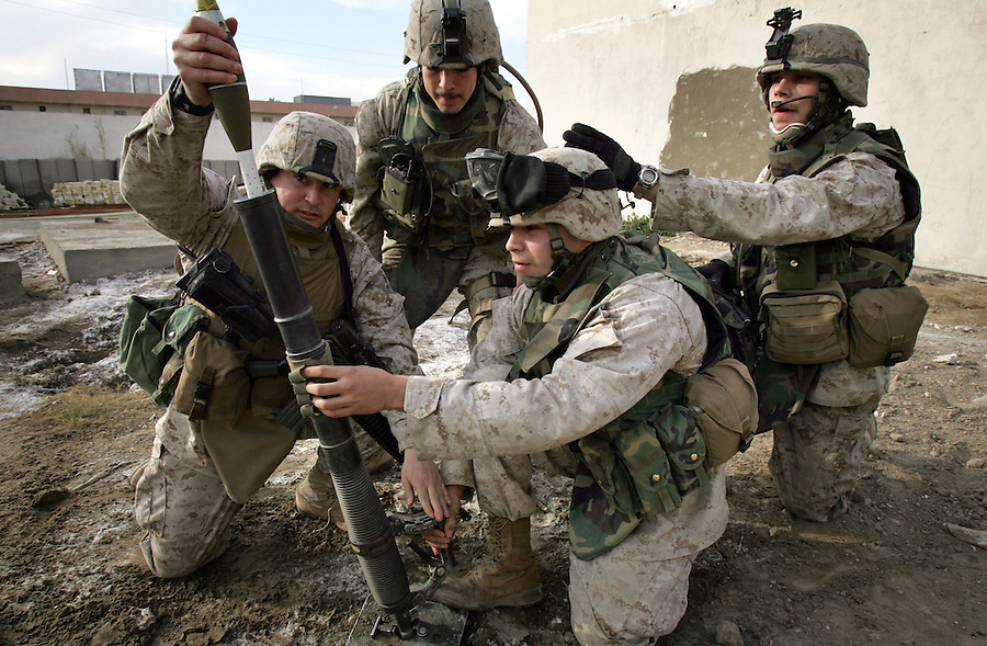 A mortar team with 2nd Platoon Golf Company 2nd Battalion 5th Marines drops 60mm mortars as the platoon tries to hold off an attack by insurgents on the Al-Anbar provincial Government Center on Saturday, Jan. 15, 2005 in Ramadi, Iraq. The Government Center houses the office of the provincial governor and administration.