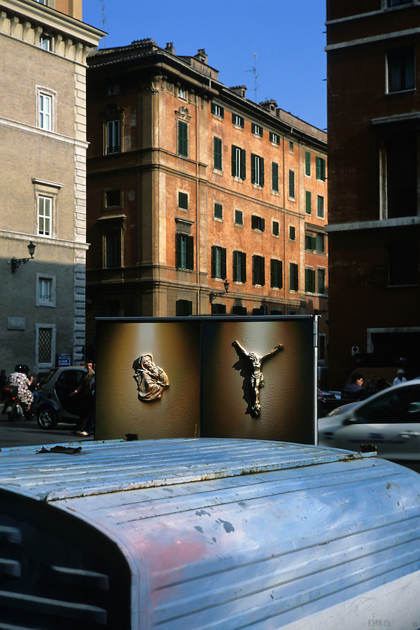 Religious iconography adorns street art in Rome, Italy.