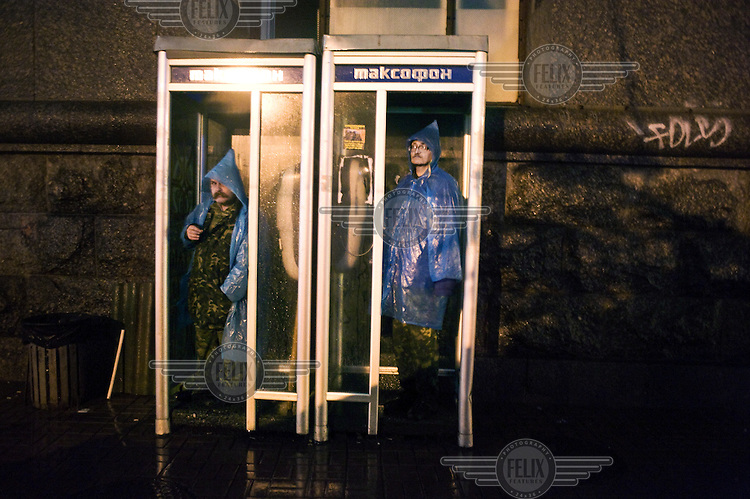 Two men in army fatigues who are working as civilian patrols on the streets of Kiev stand in a set of phone booths during a thunderstorm.