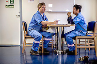 Gissur Vestergaard, from the Faroe Islands, (left) talks to his fellow electrician Danilo Songco, from Thailand, about the work plan for the day onboard the Mary Maersk, the largest container ship in the world.