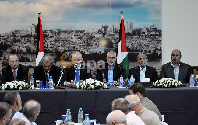 Palestinian Prime Minister Rami Hamdallah speaks during his visit to the senior Hamas leader Ismail Haniyeh, at Haniyeh's house in Gaza city on October 9, 2014. The Palestinian unity government which took the oath of office in June under technocrat prime minister Rami Hamdallah arrived to Gaza Strip on Thursday to convene the first fully meeting. Hamdallah said that the unity government will rebuild the bombed-out Gaza Strip following a seven-week Israeli offensive. Photo by Mohammed Talatene