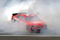 Winner Matt Kenseth, (#20) does a burnout in celebration.