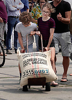 Nederland - Amsterdam - 2018.    In een klein fabriekje in Amsterdam-Noord maken de Chocolatemakers zo eerlijk en duurzaam mogelijke chocoladerepen. De ondernemers regelen zelf de inkoop en laten een zeilschip een flink deel van de cacao vervoeren, want dat is duurzamer dan een vrachtschip. Het schip de Tres Hombres wordt gelost met behulp van vrijwilligers. Naast cacao en rum wordt er ook koffie gelost. Kinderen helpen mee de zakken in de fabriek te krijgen.   Foto mag niet in negatieve / schadelijke context gepubliceerd worden.  Foto Berlinda van Dam / Hollandse Hoogte.
