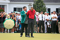 Tiger Woods (USA) is handed over the green jacket by Patrick Reid 2018 Masters champion on the putting green at The 2019 Masters , Augusta National, Augusta, Georgia, USA. 14/04/2019.<br /> Picture Fran Caffrey / Golffile.ie<br /> <br /> All photo usage must carry mandatory copyright credit (© Golffile | Fran Caffrey)