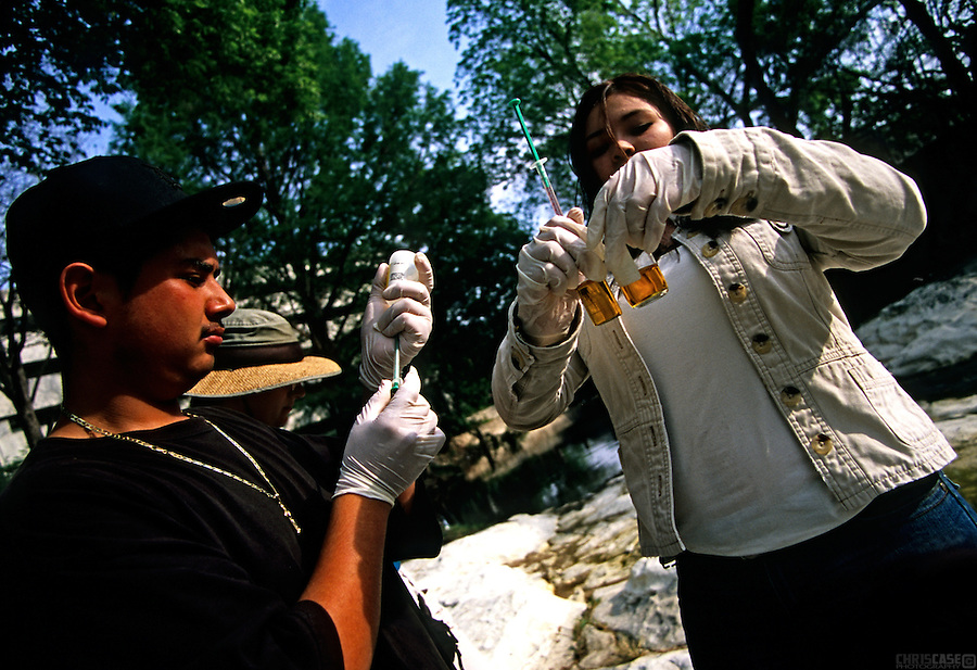 Danny Carrillo and Jessica Martinez, both members of the Austin Youth River Watch program, check for pH levels and nutrient content on Waller Creek, a tributary of the Colorado River. The program was begun in the early 1990s to give at-risk youth an opportunity to remove themselves from negative environments while learning about the river and the scientific processes of ecosystems.