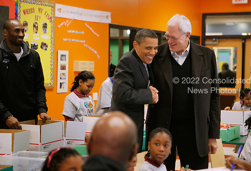 United States President Barack Obama (C) greets Los Angeles Lakers head coach Phil Jackson (R) while helping children volunteers fill care packages during a NBA Cares service event at the Boys and Girls Club at THEARC, December 13, 2010 in Washington, DC. Bryant and all the members of the 2010 NBA Championship Lakers team volunteered on projects at the club before being honored by the president for their victory. .Credit: Chip Somodevilla - Pool via CNP