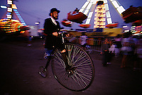 A high-wheel cyclist in period costume pedals throughout the Canfield, Ohio county fair trying to draw visitors toward an exhibit on industrial history.