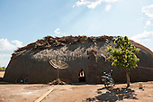 Xingu Indigenous Park, Mato Grosso, Brazil. Aldeia Matipu. Traditional Oca family house, bicycle, satelite dish, motorbike and tree. Combination of traditional culture and new technology.