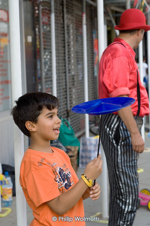 A young boy spins a plate at a circus skills workshop at Church Street Summer Festival 2005, Paddington, London.