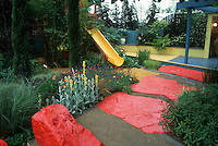 Backyard garden landscaped for children with bright colors, flowers, sliding board