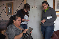 Esperanza Moctezuma giving a few dollars to her daughters Maricza and Esmeralda Moctezuma for a  trip to the store. Photo by Brendan Bannon. Painesville, Ohio march 25, 2014.