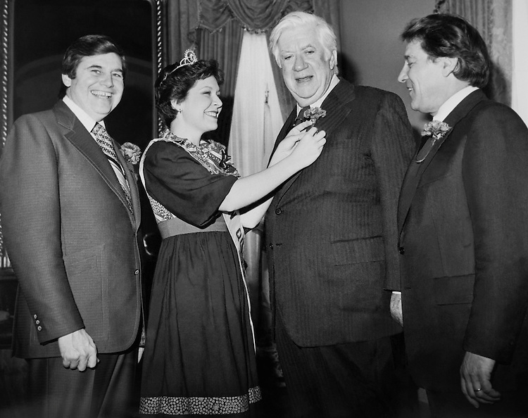 Each Congressman requires a scarlet coronation. James Puckett, Mayor of Alliance Ohio, and Carnation Queen Terry Kent, help Speaker of the House Tip O'Neill with his coronation. (Photo by Mickey Senko/CQ Roll Call)