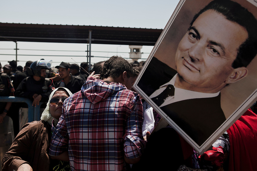 Supporters of former Egyptian President, Hosni Mubarak, listen to the court preceedings on a radio and wait to hear the verdict in his trial in front of the Cairo Police Academy, Egypt, June 2, 2012. Photo: ED GILES.
