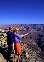 A tourist couple on the south rim gesture at the Grand Canyon. Arizona.