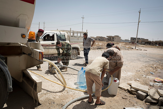 Iraqi Christian refugees, originally from Mosul, fill water containers from a tanker provided by Kurdish Zeravani soldiers in Hamdaniyah, Iraq.