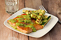 Grilled salmon fillet served with zucchini sticks and pesto sauce