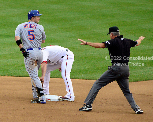 New York Mets third baseman David Wright (5) looks back for a sign second base umpire Tim Timmons after beating the tag of Washington Nationals second baseman Danny Espinosa (1) for a double in the first inning at Nationals Park in Washington, D.C. on Wednesday, July 18, 2012..Credit: Ron Sachs / CNP.(RESTRICTION: NO New York or New Jersey Newspapers or newspapers within a 75 mile radius of New York City)