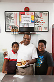 BERMUDA. St. George. Art Mel and  his kids Jade and AJ in his restaurant called Art Me's Spicy Dicy. He is holding his famous Fish Sandwich.