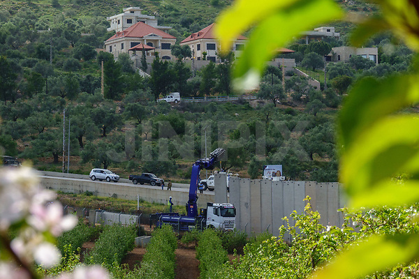 A picture taken on April 8, 2018, from the northern Israeli town of Metula, shows an Israeli crane installing sections of a concrete wall along the border, as UN forces monitor from the Lebanese side. Photo by: Ayal Margolin-JINIPIX
