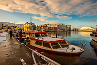 Fishing boats in harbor at Alesund, Norway. The town is famous for its art nouveau (Jugendstil) architecture. The  town was rebuilt after a fire in 1904. Alesund is in the heart of Fjord Country, at the entrance to Geirangerfjord on Norway's west coast.