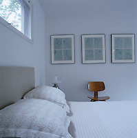 A row of prints by Andy Warhol above a mid-century bentwood chair in the simple bedroom