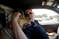 UNITED STATES - JULY 19: U.S. Capitol Police K9 Technician Andrew Maybo greets his dog Vandy after checking out a parked car on his patrol. The K9 unit serves as a visible deterrent factor - but one with a less intimidating face to the numerous tourists than the more visibly armed officers.