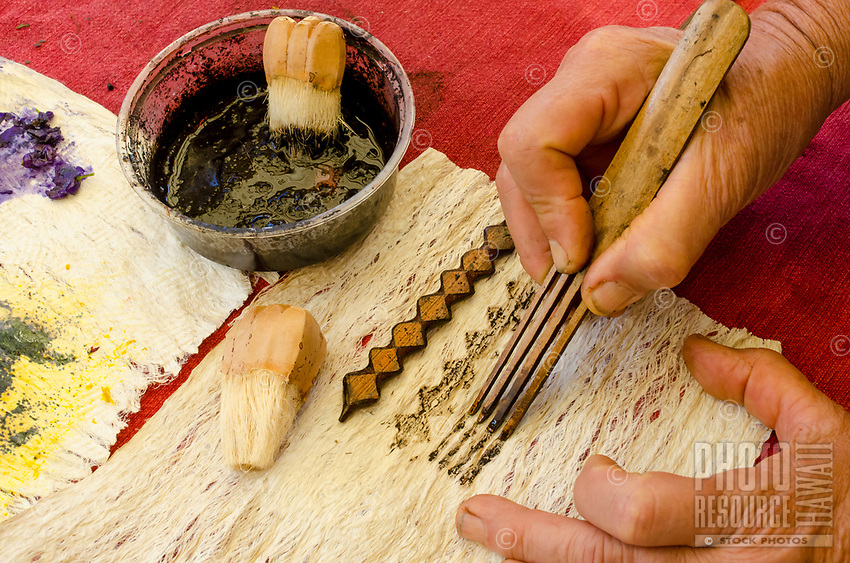 Kapa making on the Big Island: A kapa maker uses a hala brush, 'ohe kapala (bamboo stamp) and bamboo liner to apply plant dyes on to kapa.