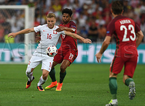 30.06.2016. Marseille, France.  Jakub Blaszczykowski (L) of Poland and Eliseu (C) of Portugal vie for the ball during the UEFA EURO 2016 quarter final soccer match between Poland and Portugal at the Stade Velodrome in Marseille, France, 30 June 2016.