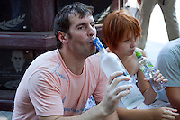 Moscow, Russia, 25/07/2010..A man drinks vodka from the bottle as hundreds of Russians gather at the grave of legendary bard singer, poet and actor Vladimir Vysotsky to mark the 30th anniversary of his death. Vysotsky, an alcoholic and heroin addict who died in 1980 aged 42 of a heart attack, is best known for his songs of Soviet prison and military life, and his acting on stage and screen. Much of his work was officially unpublished during his lifetime, and he remains a potent anti-authoritarian symbol of protest to Russians of all ages even today.