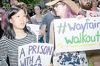 """People hold signs as Wayfair employees demonstrate in Copley Square to protest their company's sale of furniture to detainment camps for children operated by US Customs & Border Protection (CBP) on the Mexico border in Boston, Massachusetts, USA, on Wed., June 26, 2019. Wayfair is an online furniture retailer. Employees are asking for the company to set ethics standards for sales.  The Wayfair employees were joined by union representatives, PRIDE activists, and other groups in solidarity.  This action occurred the week after US government legal representatives argued that children held in CBP facilities did not need soap or beds to meet the """"safe and sanitary"""" standard of care required by law after months and years of criticism of Trump administration policies of family separation and cruel treatment of those held at its facilities."""