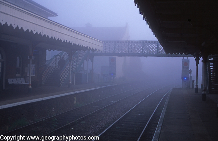 AYBR79 Foggy railway station early morning with bridge crosing to other platform