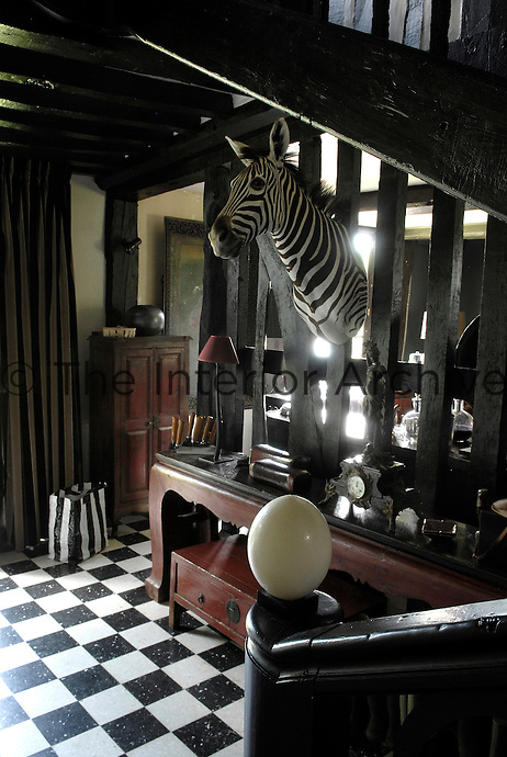 In the entrance hall a mounted zebra's head creates a striking focal point above a 1930's Chinese console table