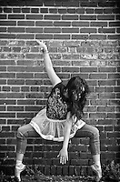 Ballerina on the tips of her toes against a brick wall in an urban environment