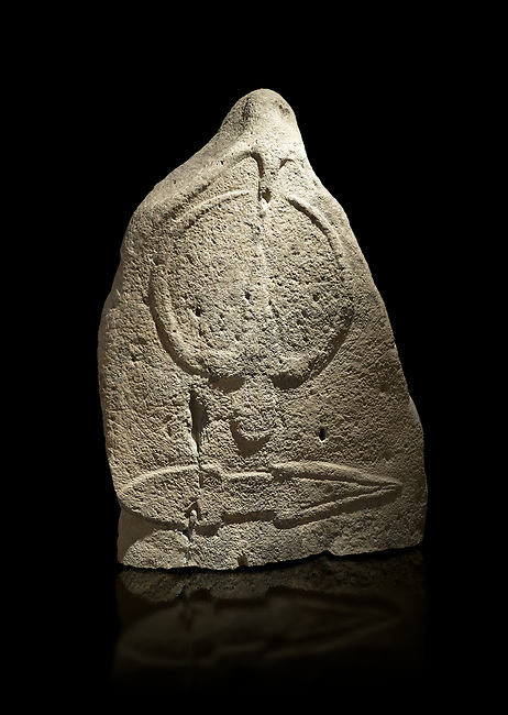 Late European Neolithic prehistoric Menhir standing stone with carvings on its face side. The representation of a stylalised male figure starts at the top with a long nose from which 2 eyebrows arch around the top of the stone. below this is a carving of a falling figure with head at the bottom and 2 curved arms encircling a body above. at the bottom is a carving of a dagger running horizontally across the menhir.  From Barrili I site, Laconi. Menhir Museum, Museo della Statuaria Prehistorica in Sardegna, Museum of Prehoistoric Sardinian Statues, Palazzo Aymerich, Laconi, Sardinia, Italy. Black background.